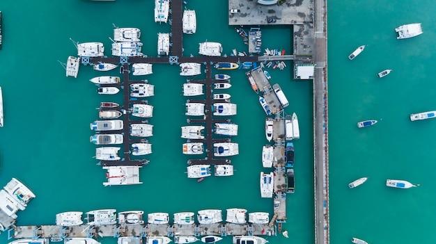 航空写真トップダウンマリーナのヨットとヨットの駐車場のドローンショット交通機関と旅行の背景の概念。 Premium写真
