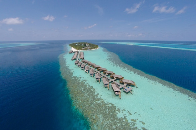Aerial view of a tropical island in turquoise water. luxurious over-water villas on tropical island resort maldives for holiday vacation background concept -boost up color processing. Free Photo