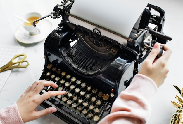 Aerial view of a woman typing on a retro typewriter blank paper Free Photo