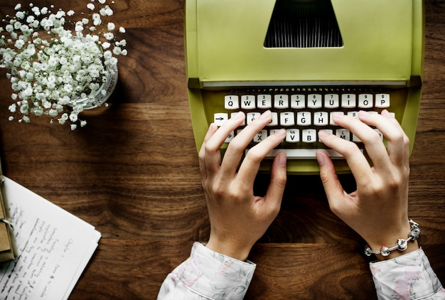 Aerial view a woman using a retro typewriter Free Photo