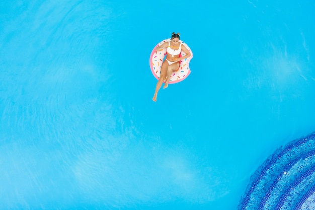 Aerial view of young beautiful girl in a white  bikini relaxing on inflatable donut in the pool. summer vacation background Premium Photo