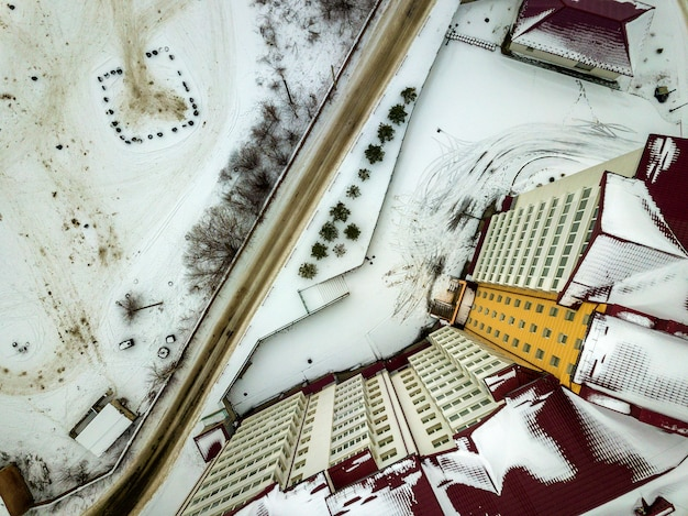Aerial winter top view of modern big apartment building in suburb area at narrow dirty road and snowy field. Premium Photo