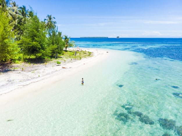 Aerial: woman getting out of caribbean sea turquoise water tropical beach island Premium Photo