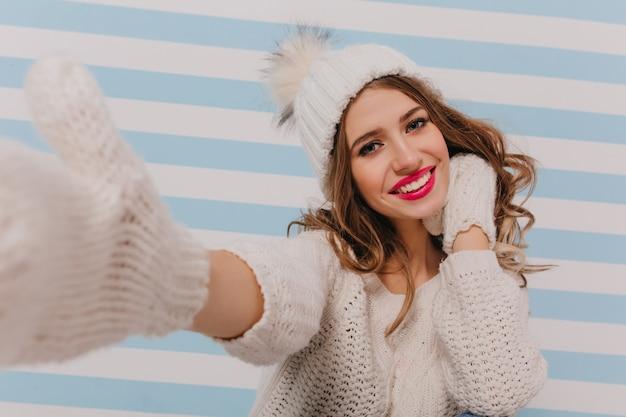 愛情深く、夢のような、巻き毛の茶色の髪のロマンチックな表情で、自分撮りのポーズをとっています。かわいい、暖かいニット帽とセーターの女性の屋内の肖像画 無料写真
