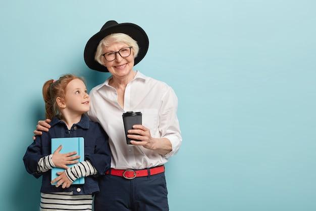 帽子をかぶった愛情のこもった白髪の祖母は、小さな女性の子供を抱きしめ、孫娘を愛し、持ち帰り用のコーヒーを飲みます。手帳を持った好奇心旺盛な小さな子供は、賢い老婆からのアドバイスを聞きます。 無料写真