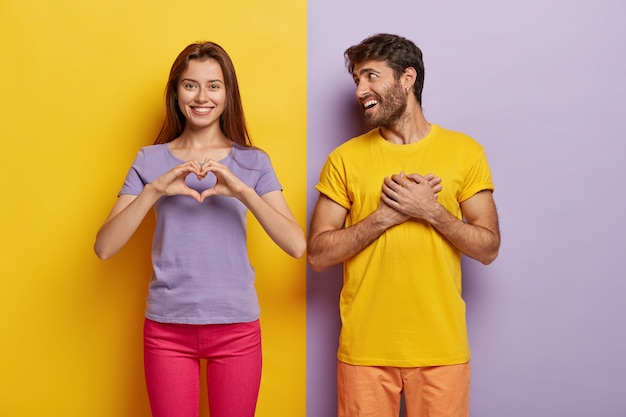 Affectionate woman shows heart gesture, says be my valentine to boyfriend, confesses in love Free Photo
