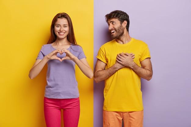 Ласковая женщина показывает жест сердца, говорит парню «будь моей валентинкой», признается в любви Бесплатные Фотографии