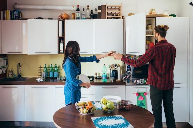 Ласковая молодая пара приготовления пищи в кухне дома Premium Фотографии