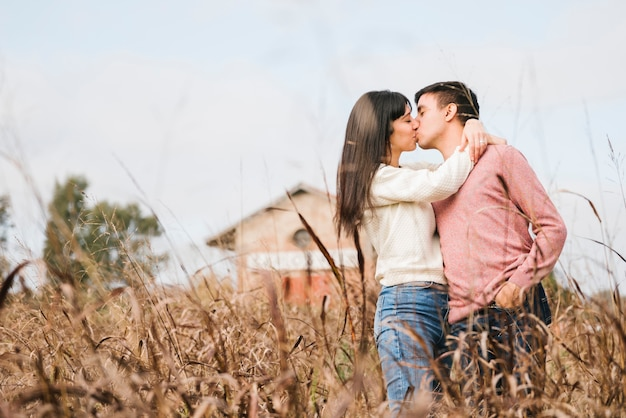 Affectionate young couple standing kissing Free Photo