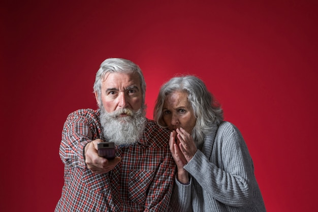 Afraid woman sitting near the senior man changing the channel with remote control against red background Free Photo