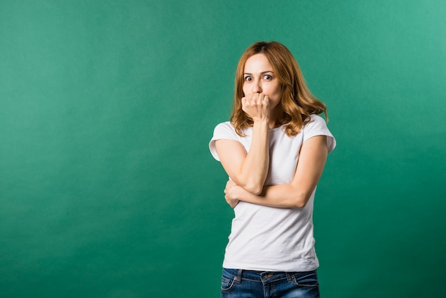 Afraid young woman covering her mouth against green backdrop Free Photo