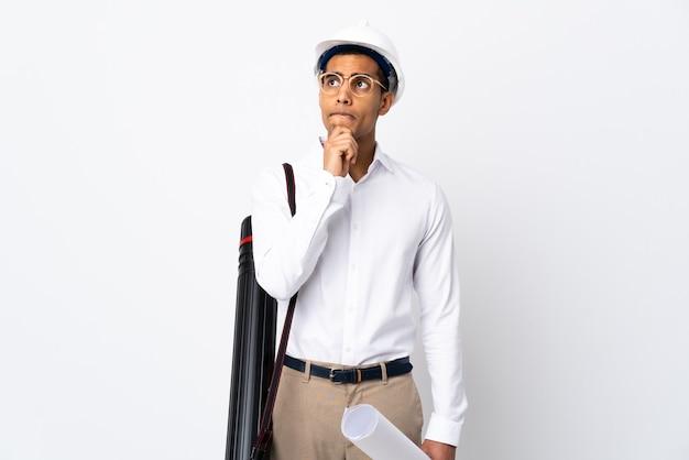 헬멧과 격리 된 흰색 배경 위에 청사진을 들고 아프리카 계 미국인 건축가 남자 _ 의심을 가지고 생각 프리미엄 사진