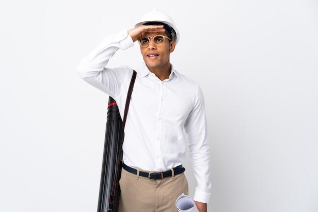 헬멧과 격리 된 흰색 배경 위에 청사진을 들고 아프리카 계 미국인 건축가 남자 _ 뭔가를 찾고 손으로 멀리 찾고 프리미엄 사진