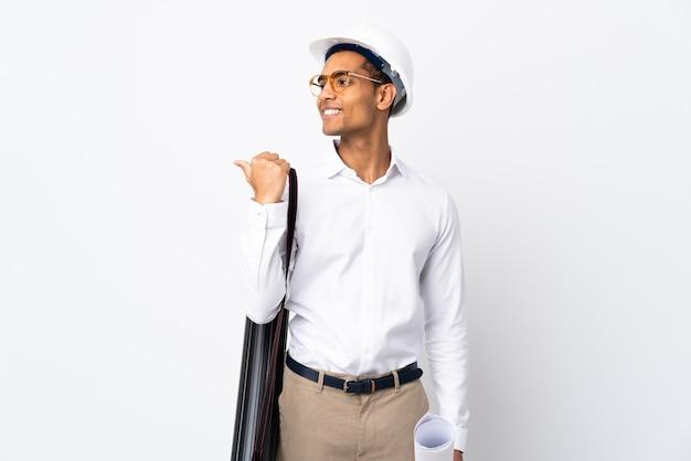 헬멧과 격리 된 흰색 배경 위에 청사진을 들고 아프리카 계 미국인 건축가 남자 _ 제품을 제시하기 위해 측면을 가리키는 프리미엄 사진