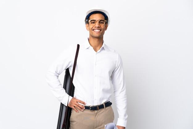 헬멧과 격리 된 흰색 배경 위에 청사진을 들고 아프리카 계 미국인 건축가 남자 엉덩이에 팔을 포즈와 미소 프리미엄 사진