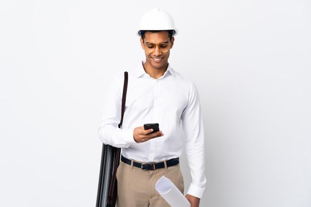 헬멧과 격리 된 흰색 배경 위에 청사진을 들고 아프리카 계 미국인 건축가 남자 _ 모바일로 메시지 보내기 프리미엄 사진