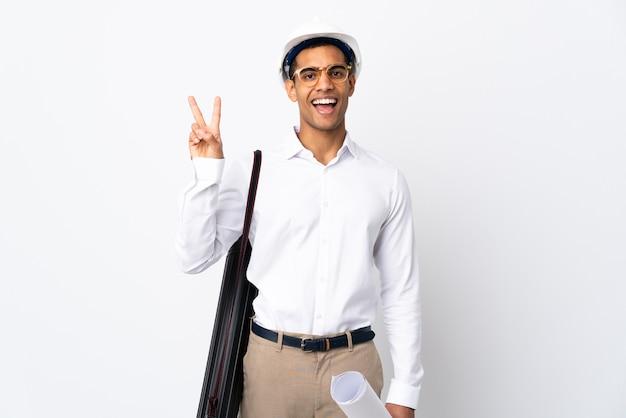 헬멧과 격리 된 흰색 배경 위에 청사진을 들고 아프리카 계 미국인 건축가 남자 웃 고 승리 기호를 보여주는 프리미엄 사진