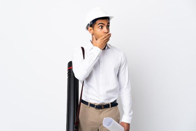 헬멧과 격리 된 흰 벽 위에 청사진을 들고 아프리카 계 미국인 건축가 남자 _ 측면을 보면서 깜짝 제스처를 하 프리미엄 사진