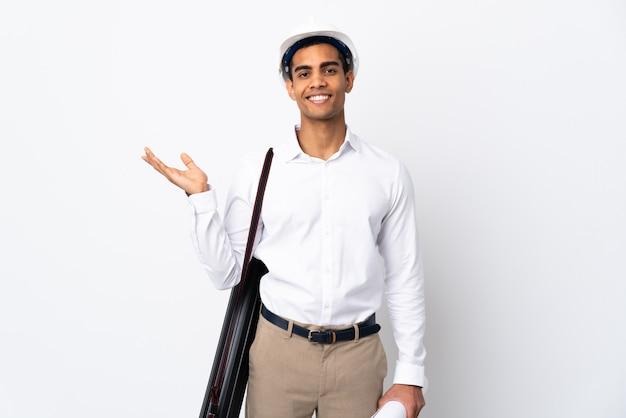 헬멧과 격리 된 흰 벽 위에 청사진을 들고 아프리카 계 미국인 건축가 남자 _와 초대 측면에 손을 연장 프리미엄 사진