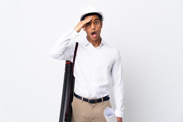 헬멧과 격리 된 흰 벽 위에 청사진을 들고 아프리카 계 미국인 건축가 남자 _ 뭔가 실현하고 솔루션을 의도 프리미엄 사진