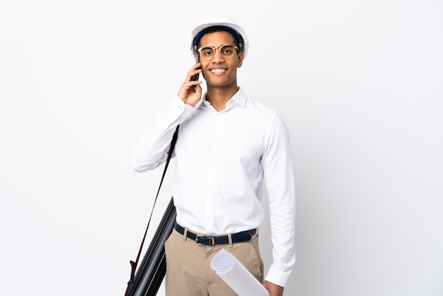 헬멧과 격리 된 흰 벽 위에 청사진을 들고 아프리카 계 미국인 건축가 남자 _ 누군가와 휴대 전화와 대화를 유지 프리미엄 사진