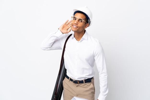 헬멧과 격리 된 흰 벽 위에 청사진을 들고 아프리카 계 미국인 건축가 남자 _ 귀에 손을 넣어 뭔가를 듣고 프리미엄 사진