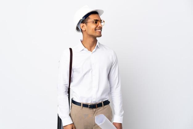 헬멧과 격리 된 흰 벽에 청사진을 들고 아프리카 계 미국인 건축가 남자 _ 측면을보고 웃 프리미엄 사진