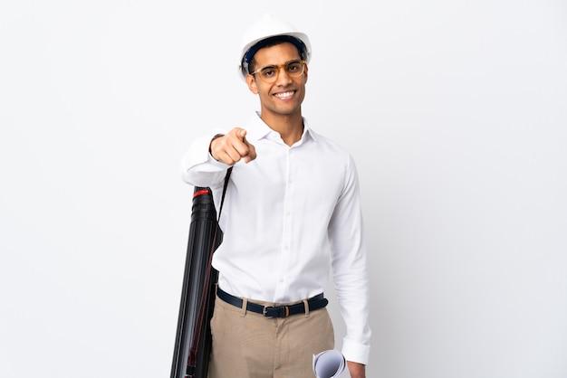 헬멧과 격리 된 흰 벽 위에 청사진을 들고 아프리카 계 미국인 건축가 남자 _ 행복 한 표정으로 앞을 가리키는 프리미엄 사진