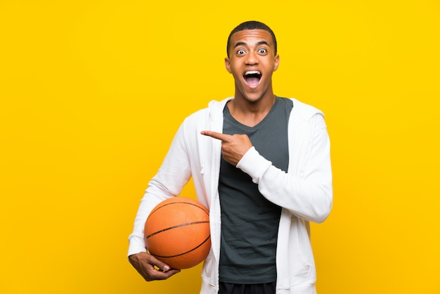 African american basketball player man surprised and pointing side Premium Photo