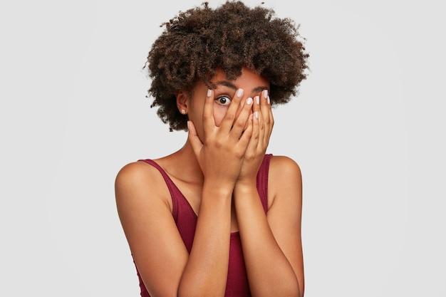 L'afroamericano bella giovane femmina sbircia anche se le dita, copre il viso con entrambe le mani, ha un'espressione spaventata quando nota qualcosa di terribile o spaventoso Foto Gratuite