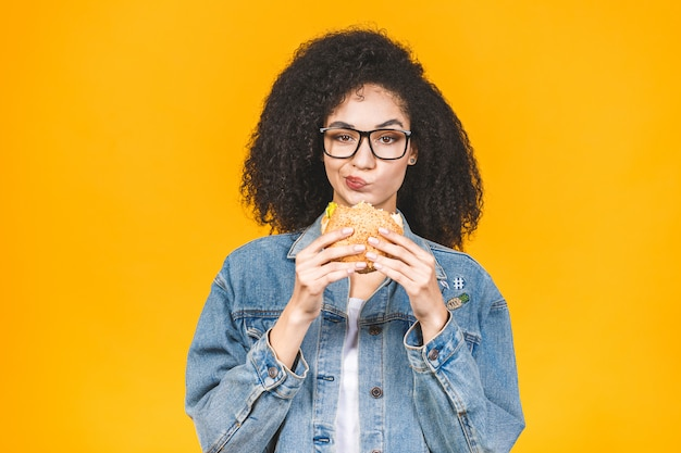 African american black young woman eating hamburger isolated on yellow background. Premium Photo