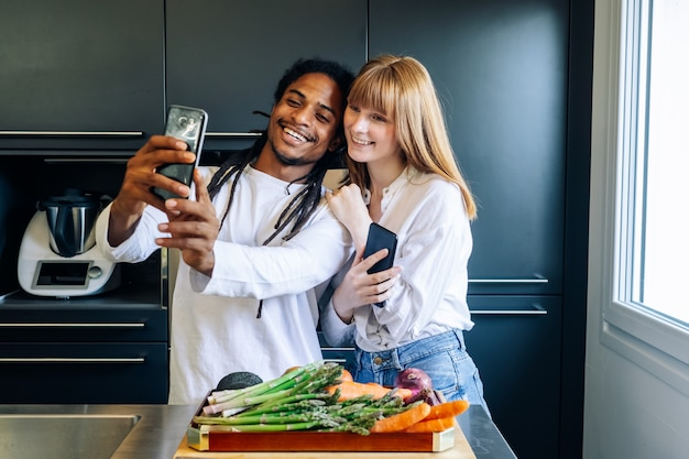 African american boy and white girl making a selfie in the kitchen Premium Photo