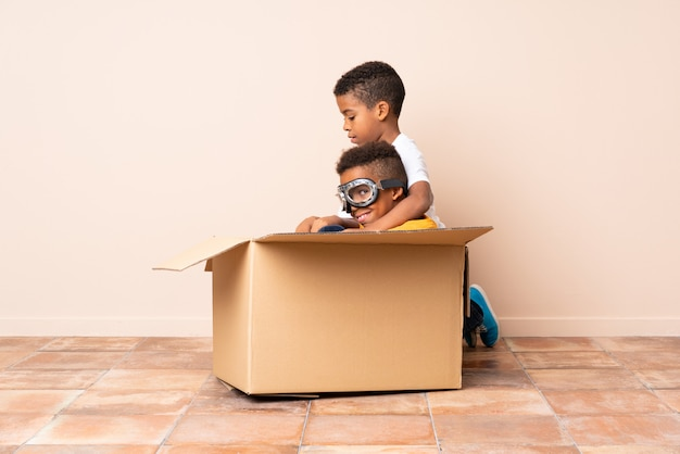 African american brothers playing, boy inside a cardboard box with aviator glasses Premium Photo