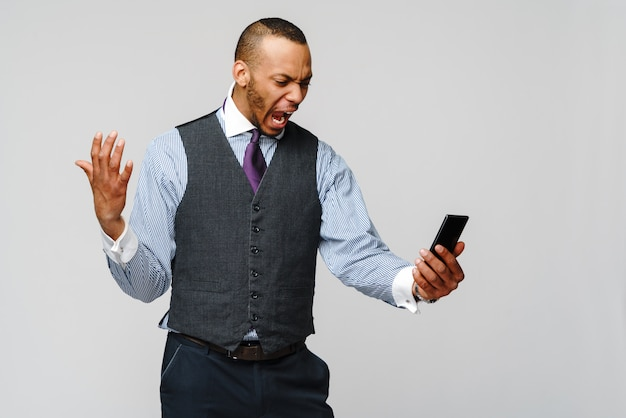 Афро-американский деловой человек разговаривает по мобильному телефону - стресс и негатив. Premium Фотографии