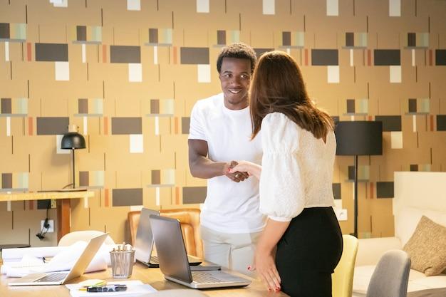 アフリカ系アメリカ人のデザイナーの笑顔と挨拶の女性クライアント 無料写真