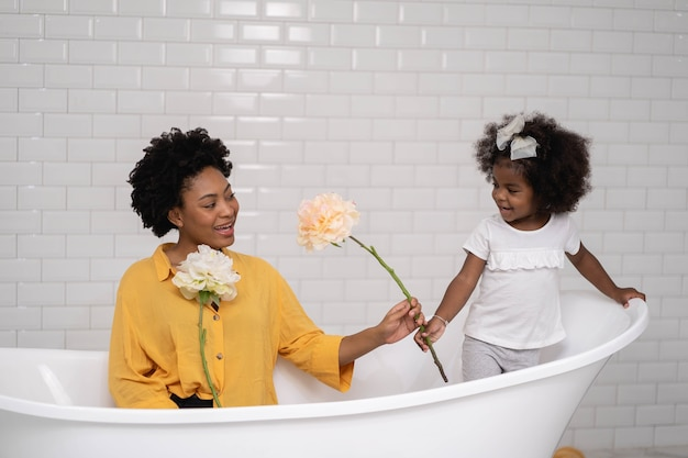 African american family, happy mother and baby daughter having fun and playing together at the bathroom Premium Photo