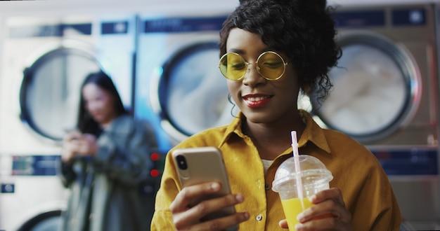 アフリカ系アメリカ人の女の子がストローでオレンジジュースを飲んだり、電話でテキストメッセージを送ったり、服がきれいになるのを待っています。 Premium写真