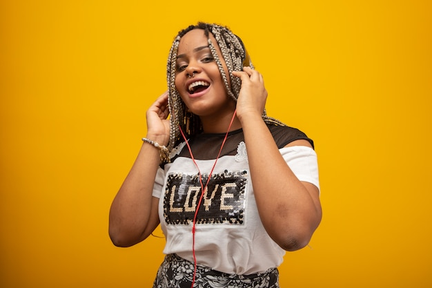 African american girl listening to music on a headphones on yellow Premium Photo