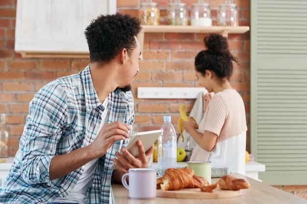 Афроамериканец смотрит на жену или девушку, просит ее дать банан, сидит за кухонным столом, пользуется современным планшетным компьютером Бесплатные Фотографии
