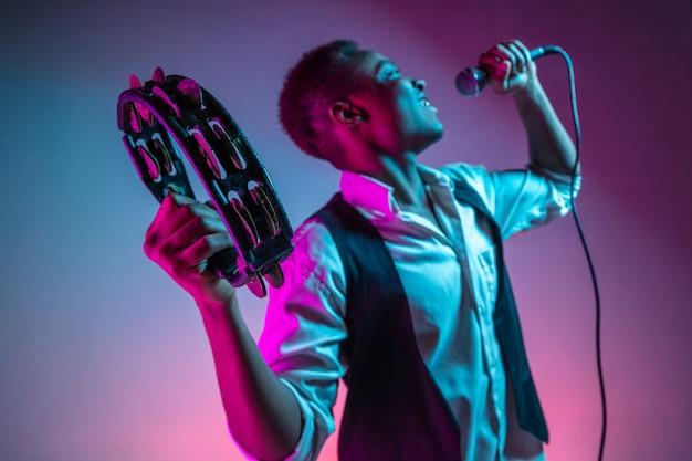 タンバリンを演奏し、歌うアフリカ系アメリカ人のハンサムなジャズミュージシャン。 無料写真