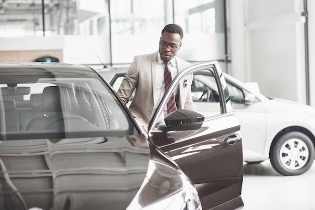 Un afroamericano ispeziona l'auto presso il concessionario di automobili. buon affare. Foto Gratuite