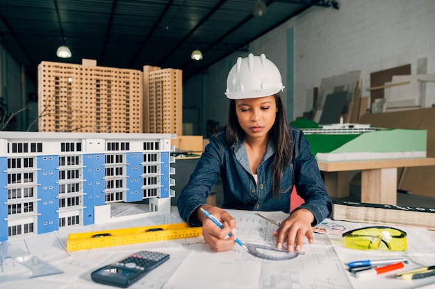African-american lady in safety helmet working near model of building Free Photo