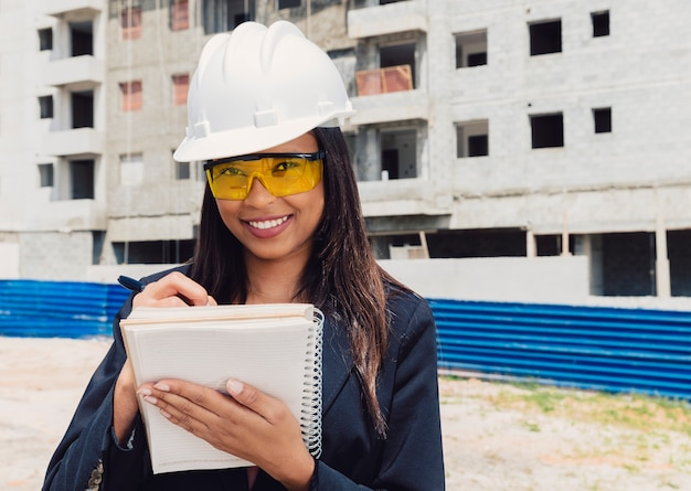 African american lady in safety helmet writing in notebook near building under construction Free Photo