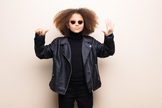 平らな壁にアフリカ系アメリカ人の少女。クールなコンセプト Premium写真