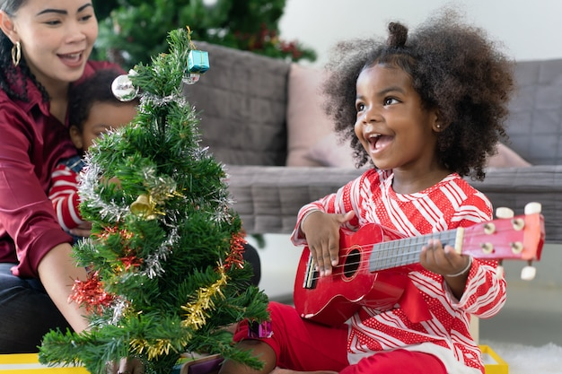 African american little girl playing ukulele guitar celebrated christmas at home with her mother Premium Photo