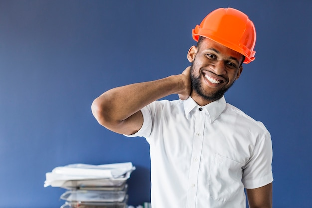 African american male architect standing against blue wall at workplace Free Photo
