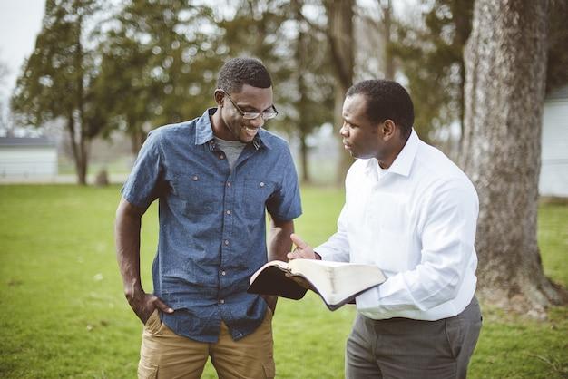 公園に立って聖書について話し合っているアフリカ系アメリカ人の男性の友人 無料写真