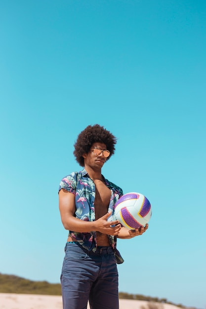 African american male holding ball on beach Free Photo