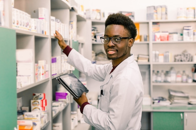 African american male pharmacist using digital tablet during inventory in pharmacy. Premium Photo