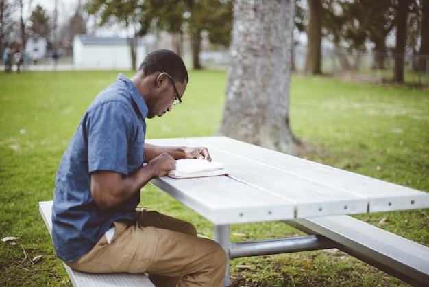 Афро-американский мужчина сидит за столом и читает библию Бесплатные Фотографии